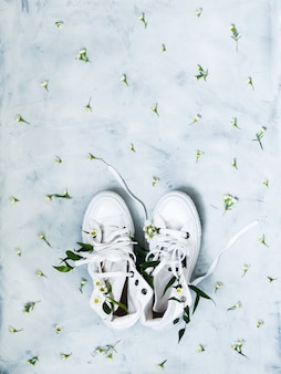 Top view of white gumshoes with fresh flowers on grey background