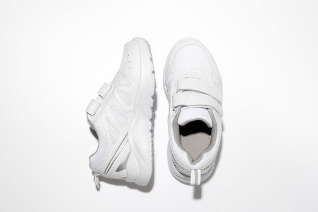 Top view white kid sneakers with velcro fasteners one sneaker on the side isolated on a white backgr...