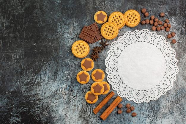 Vista dall'alto di pizzo bianco con layout a forma di mezzaluna di dolci su sfondo grigio