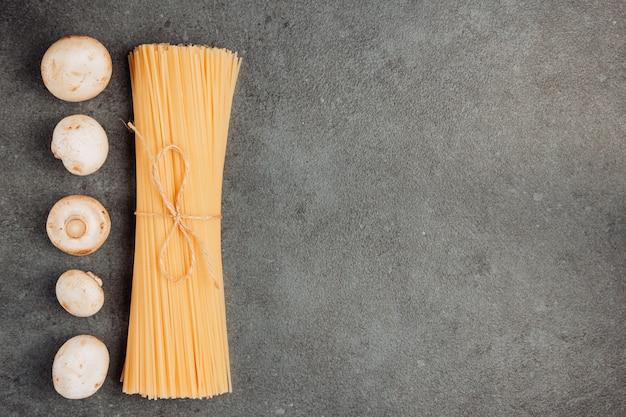 トップビューの白いキノコと灰色のテクスチャ背景にスパゲッティパスタの束。テキストの水平方向のスペース