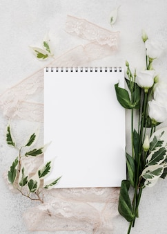 Top view white notepad with flowers on the table