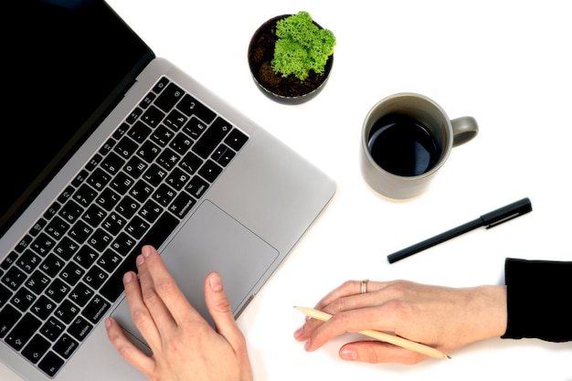 Стол офисного стола вид сверху белый с пустой тетрадью, клавиатурой компьтер-книжки компьютера, ручкой, заводом и другими канцелярскими принадлежностями. чашка кофе с копией пространства, плоская планировка. руки женщины с телефоном.