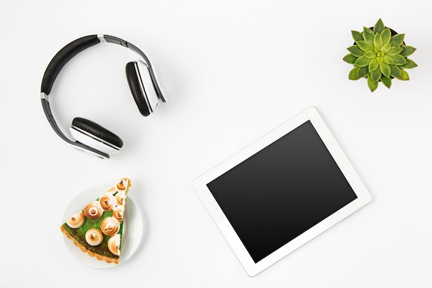 Top view of white office workspace with tablet