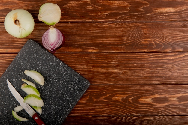Top view of white onion slices and knife on cutting board with whole ones and half cut red onion on wooden background with copy space