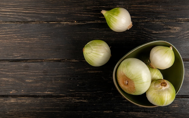 Top view of white onions in bowl on wooden background with copy space