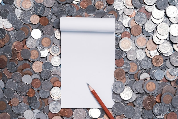 Top view of white paper book with a red pencil on a pile of coins