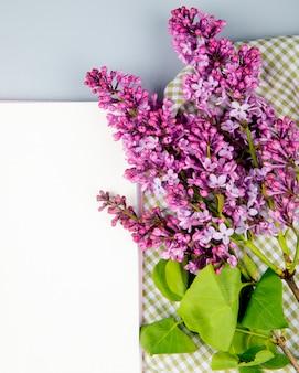Vista superiore degli strati del libro bianco e dei fiori lilla su fondo bianco