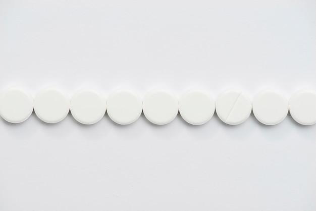 Disposizione di pillole bianche vista dall'alto