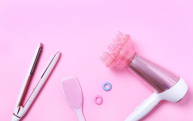 Top view of white and pink hair dryer, straightening iron, pink hair brush and accessories on pink . flat lay,hair care concept.professional hair style tool.