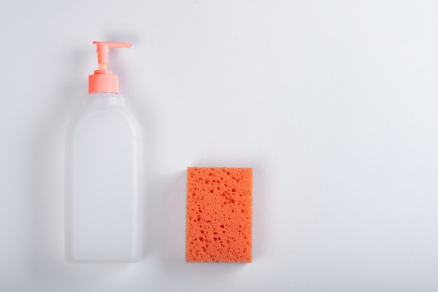 ディスペンサー、コピースペースと白い背景の上のオレンジ色のスポンジと上面図白いプラスチック家庭用ボトル