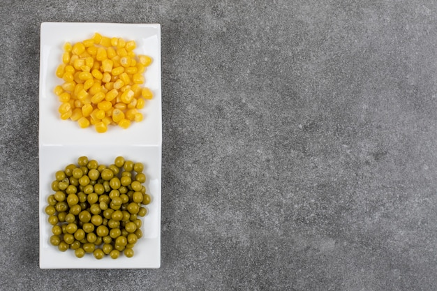 Top view of white plate full with canned pea and corn
