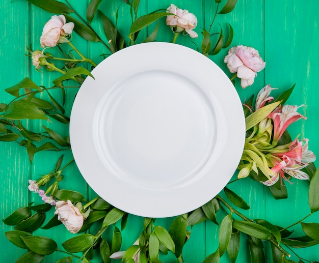 Top view of white plate on light pink flowers with leaf branches on a green surface