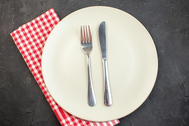 Вид сверху белая тарелка с вилкой и ножом на темной поверхности