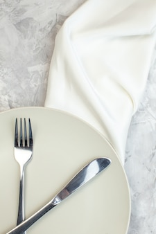 Top view white plate with fork and knife on light background kitchen food glass femininity colour horizontal ladies