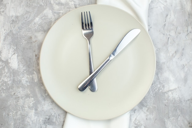Top view white plate with fork and knife on light background kitchen food glass femininity colour meal horizontal ladies