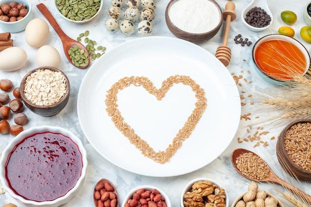 上面図白い生地の色のケーキにゼリーの卵のさまざまなナッツと種子が付いた白いプレート甘い写真ビスケットシュガーナッツ