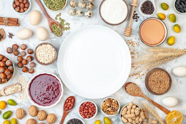 上面図白い生地の砂糖色のビスケットケーキの甘いナッツの写真にゼリーの卵のさまざまなナッツと種子が付いた白いプレート
