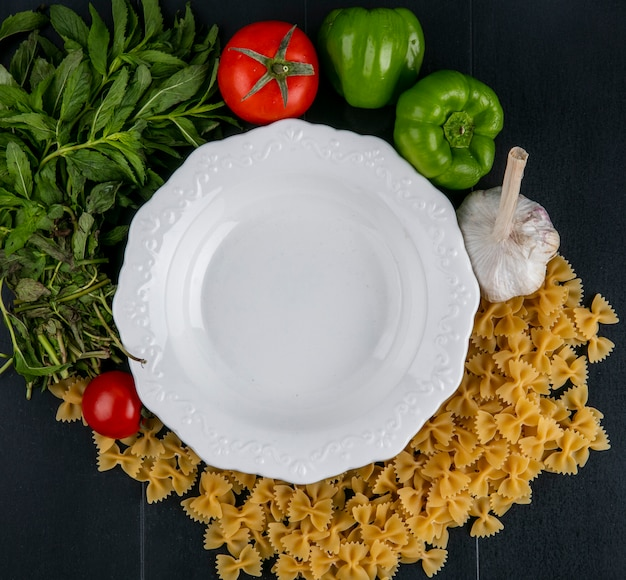 Top view of white plate with raw pasta tomatoes garlic and bell pepper with mint on a black surface