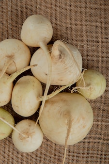 Top view of white radishes on sackcloth background