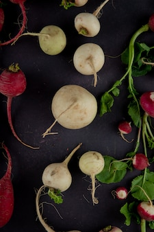 Top view of white radishes with red ones on maroon background