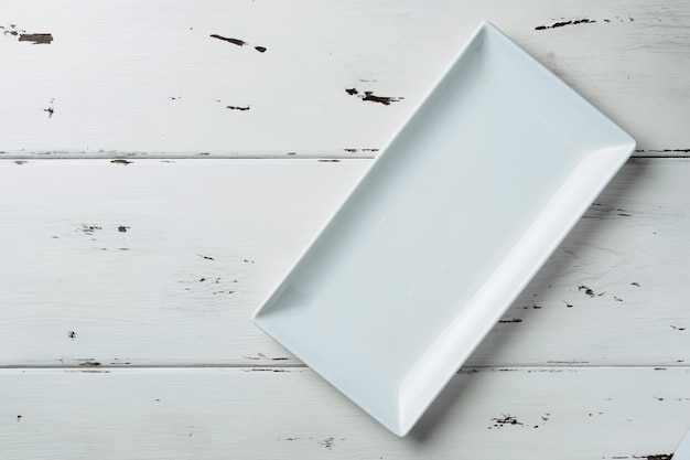 Top view of a white rectangular plate on a white wooden background.