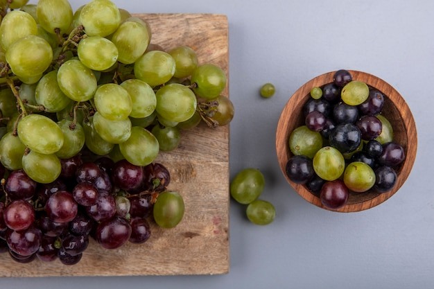 Top view of white and red grapes on cutting board and bowl of grape berries on gray background