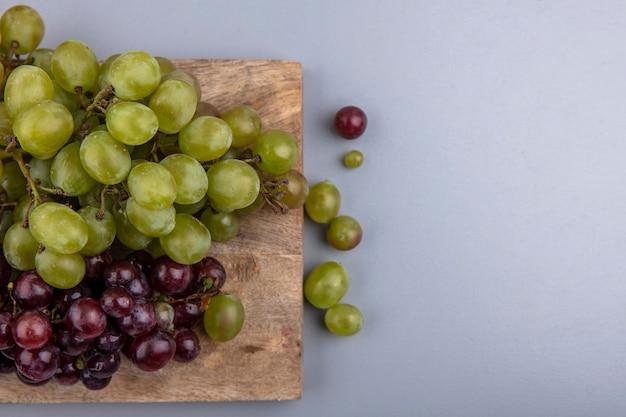Vista dall'alto di uve bianche e rosse sul tagliere e su sfondo grigio con spazio di copia