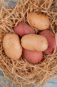 Vista superiore delle patate bianche e rosse in nido su superficie di legno