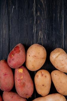Vista superiore delle patate bianche e rosse su legno con lo spazio della copia