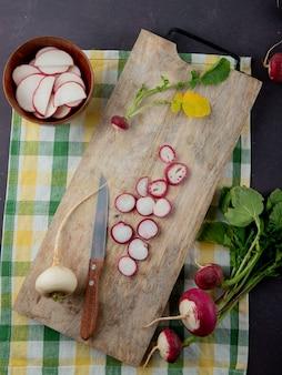 Vista superiore di ravanelli bianchi e rossi sul tagliere con coltello sulla superficie del panno e sfondo marrone