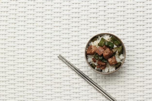 사이코로 흑후추 비프 스테이크와 그린 파프리카를 곁들인 탑 뷰 백미. 밥그릇과 같은 그릇에 제공됩니다. 텍스트를 위한 공간 복사