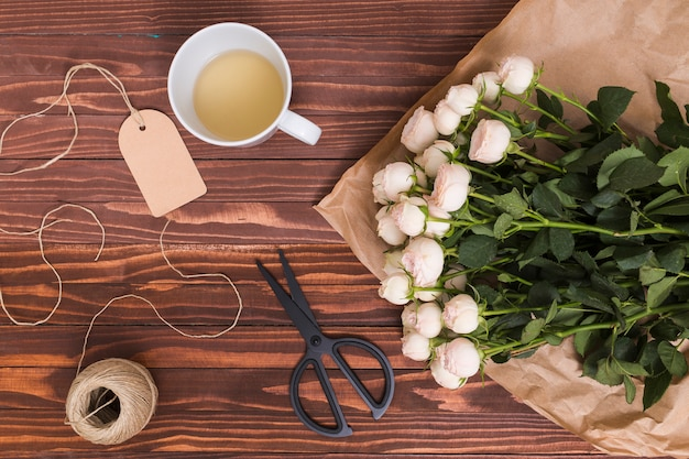 Top view of white roses; lemon tea; string and scissor; price tag above wooden textured backdrop