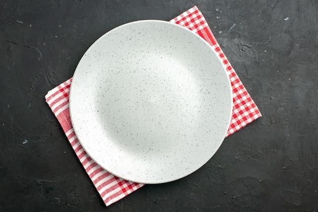 Вид сверху белая круглая тарелка на салфетке на темном столе