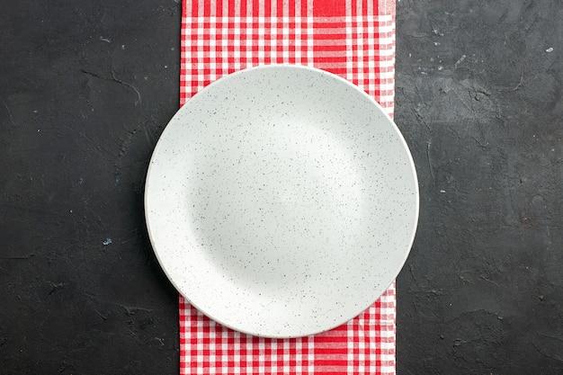 어두운 테이블 복사 장소에 빨간색과 흰색 체크 무늬 냅킨에 상위 뷰 흰색 둥근 접시