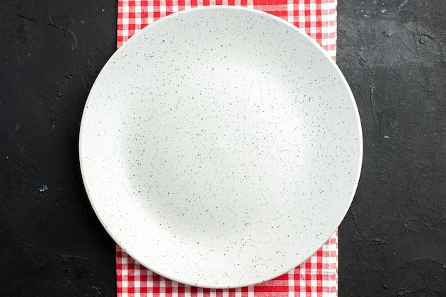 Top view white round plate on red and white checkered napkin on dark table