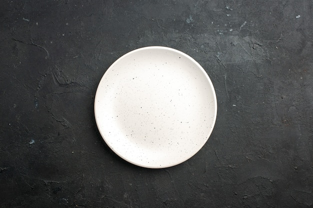 Top view white salad plate on dark table free space