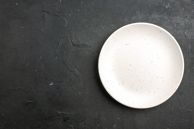 Top view white salad plate on dark table with free space
