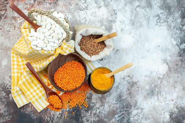Vista dall'alto semi bianchi con lenticchie arancioni e pepe su superficie chiara