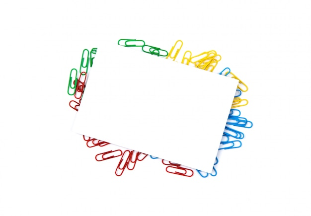 Top view of a white sheet of paper lying on paper clips. copy space for text