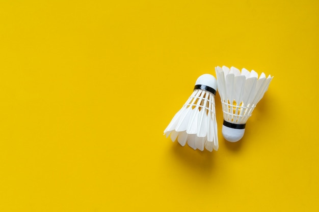 Top view of white shuttlecocks on yellow color background