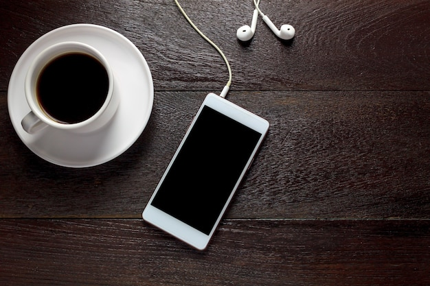 Top view white smartphone,black coffee,earphones on wood table with copy space.