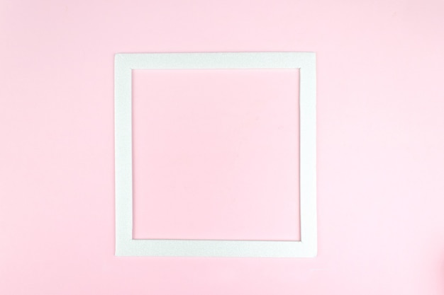 Top view of white square frame on pink, minimalistic concept. square empty card mockup.