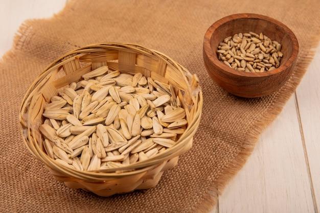 Vista dall'alto di semi di girasole bianchi su un secchio su un panno di sacco con semi di girasole sgusciati su una ciotola di legno su un tavolo di legno beige