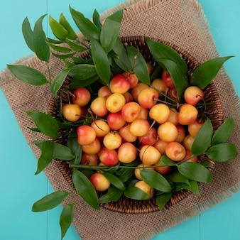 ターコイズブルーのテーブルにベージュのナプキンにバスケットの枝の葉と上面の白い甘いチェリー