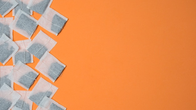 Top view of white tea bags on an orange background with space for writing the text