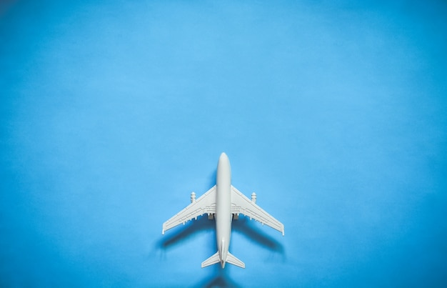 Top view of white toy airplane model over blue color background