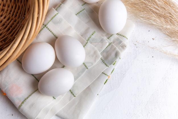 Vista dall'alto di uova intere bianche con cesto sulla superficie bianca