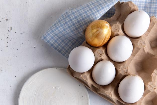 Vista dall'alto di uova intere bianche con quella dorata sulla superficie bianca