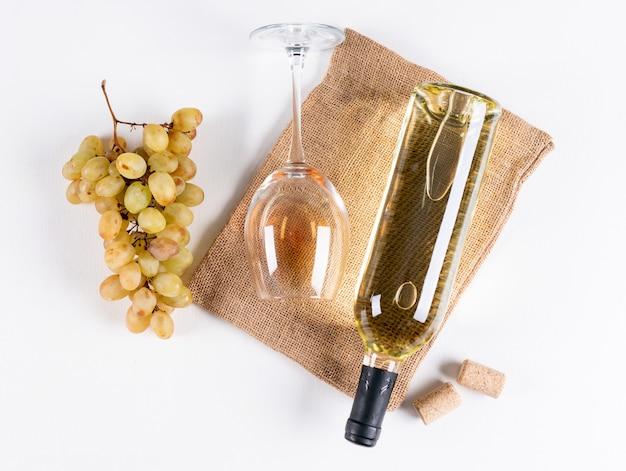 Вид сверху белое вино в бутылке и бокал с виноградом на льняной сумке на белой горизонтали