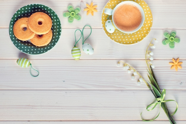Top view on white wooden table with espresso cup, plate of cookies, easter eggs and spring flowers, copy-space